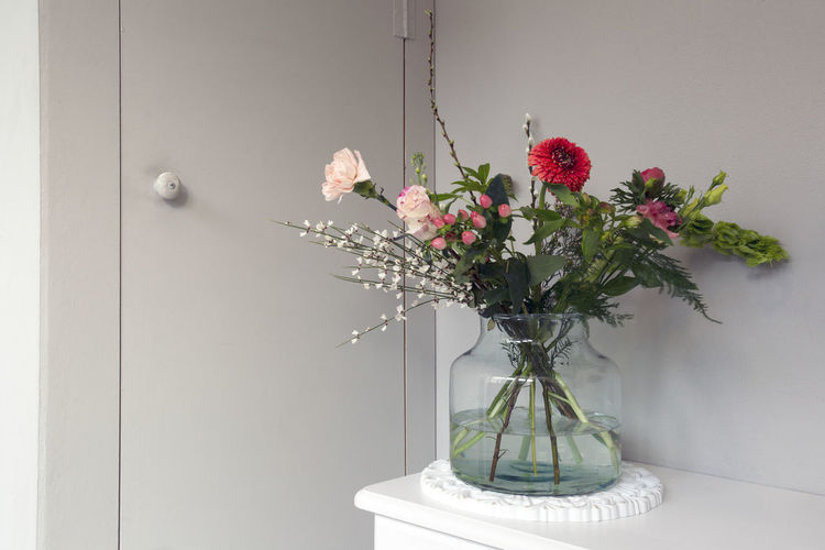 Flowers in vase against wall at home
