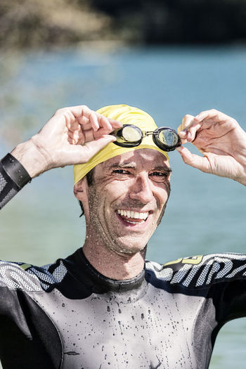 Portrait Of Happy Male Triathlete Removing Goggles While Standing Against River