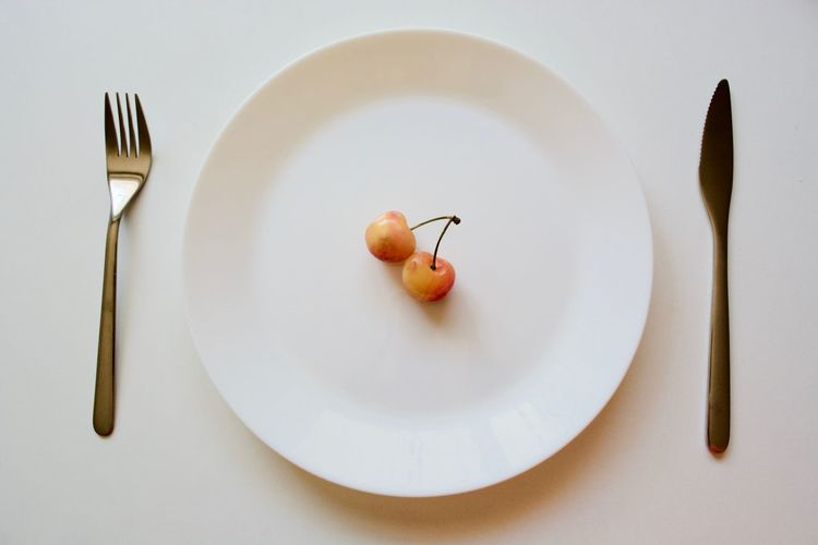 High angle view of cherries with cutleries in plate on white background