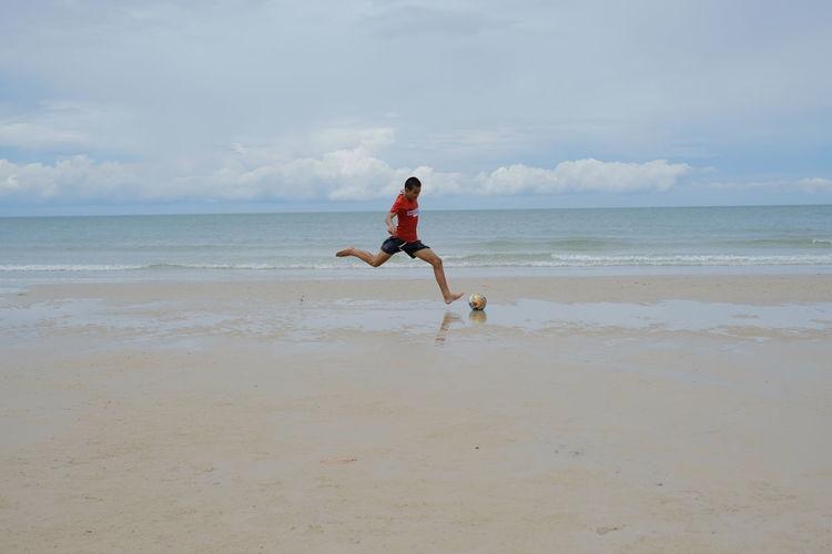 Full length of man playing on beach against sky