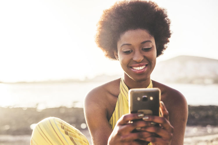 Young Woman Smiling While Using Phone At Beach During Sunset