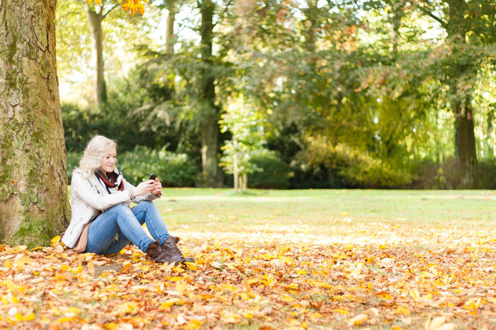Attractive young woman using smart phone Autumnal Colours Autumnal Leaves Autumnal Mood Casual Clothing Caucasian Cell Phone  Communication Fall Colors Fall Season Mobile Phone Outside Person Smart Phone Smartphone Text Message Text Messaging Young Adult Young Woman Mobile Conversations