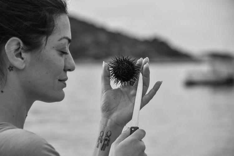 Woman holding sea urchins by lake