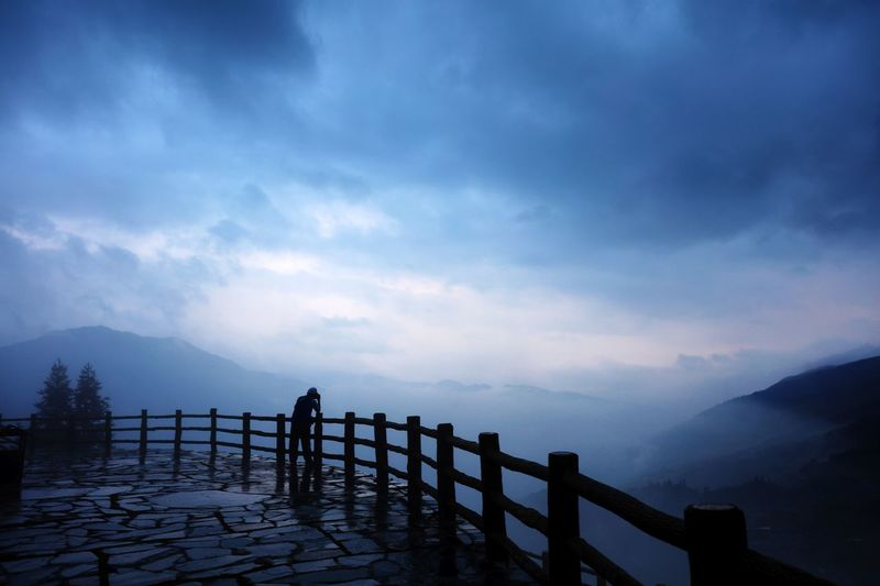 Silhouette Person At Observation Point Against Cloudy Sky During Foggy Weather