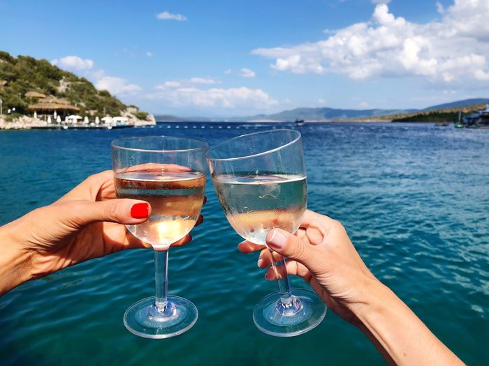 Summer Wine Water Food And Drink Hand Drink Refreshment Glass Human Hand Alcohol Sky Real People Leisure Activity Lifestyles Day Sea Celebratory Toast