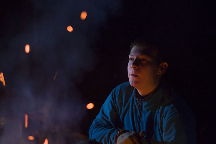 Young man by campfire at night