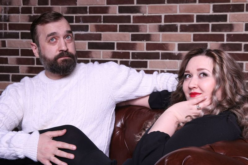 Thoughtful Couple Sitting On Sofa Against Brick Wall