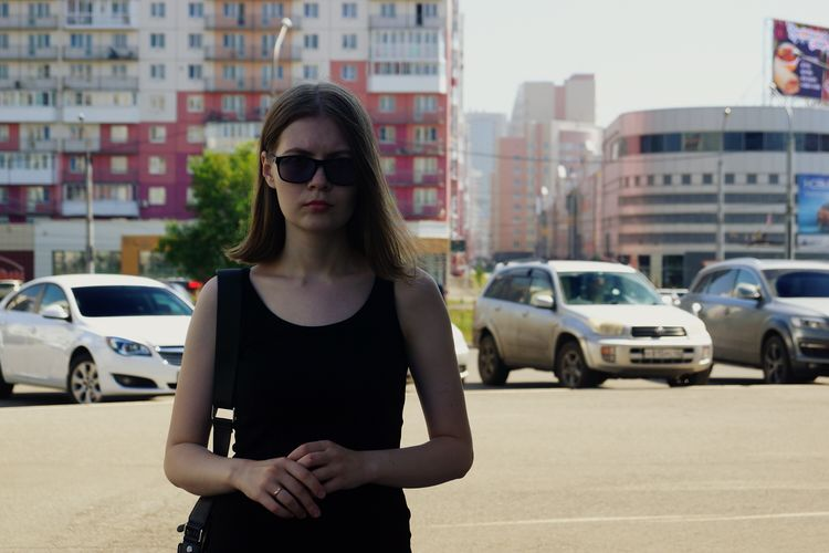 Woman in sunglasses standing on street in city