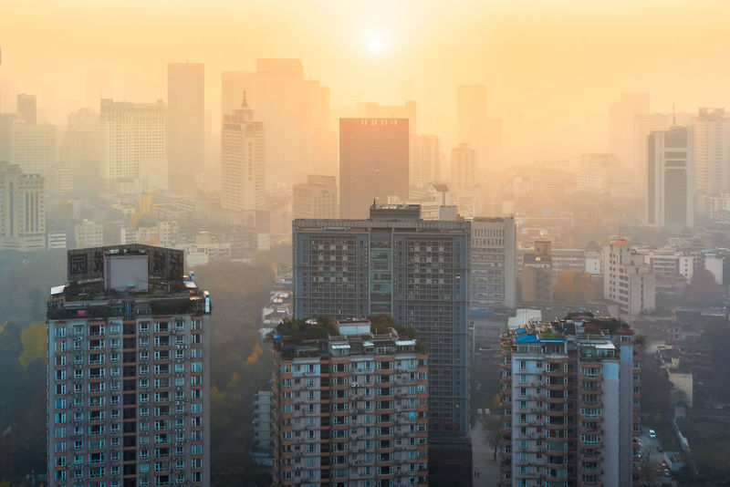 Pollution at sunrise in a chinese city. Architecture Building Exterior Built Structure City Cityscape Development Downtown District Haze High Angle View Modern Pollution Sky Skyscraper Sunrise Tall Tall - High Tower Urban Scene