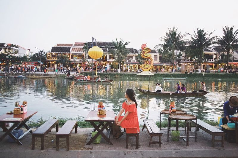 People sitting on table by lake against sky