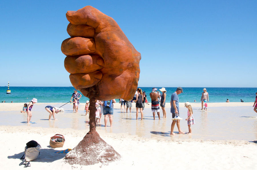 Large fist sculpture with families and the Indian Ocean during the Sculptures by the Sea arts festival at Cottesloe Beach in Western Australia. Art Artistic Arts And Entertainment ArtWork Beach Cottesloe Creativity Event Families Festival Fist Hand Horizon Over Water Indian Ocean Interactive  Leisure Activity Modern Outdoors Recreational Pursuit Sand Sculpture Sculptures By The Sea Tourists Waterfront Western Australia