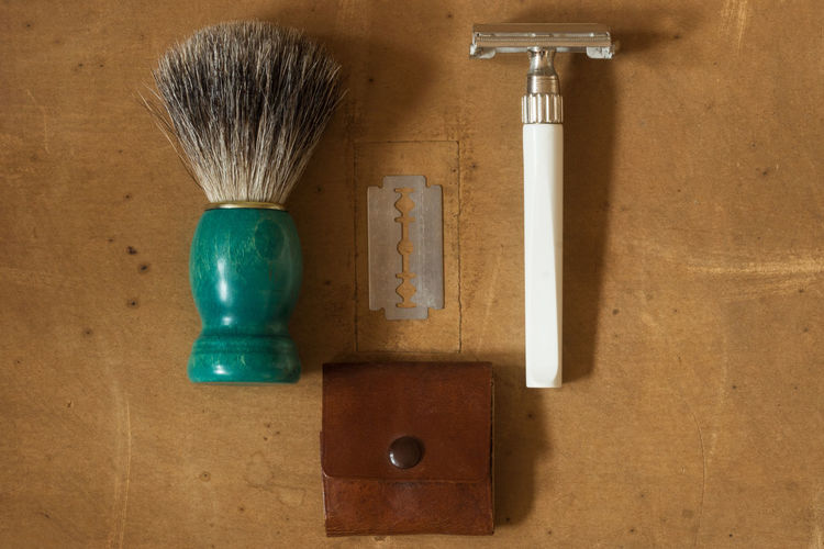High Angle View Of Shaving Equipment On Wooden Table