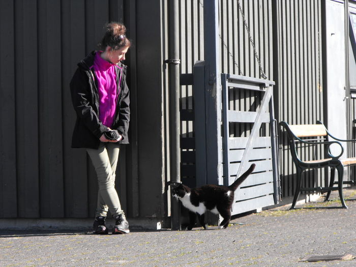 Woman with cat standing on footpath