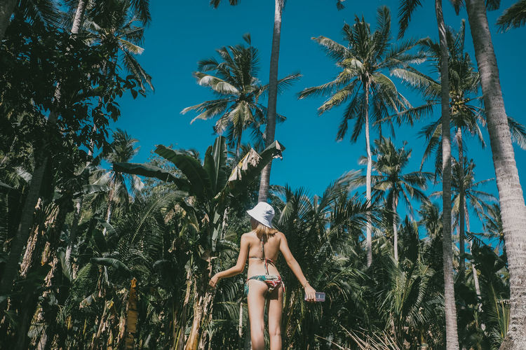 Woman in bikini standing against palm trees