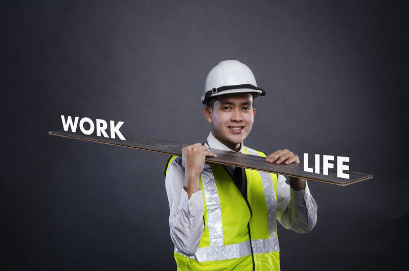 happy face young engineer or manager with white safety helmet holding wooden board. One Person Studio Shot Portrait Men Standing Looking At Camera Young Adult Front View Helmet Safety Young Men Holding Occupation Smiling Protection Clothing Black Background Security Headwear Uniform