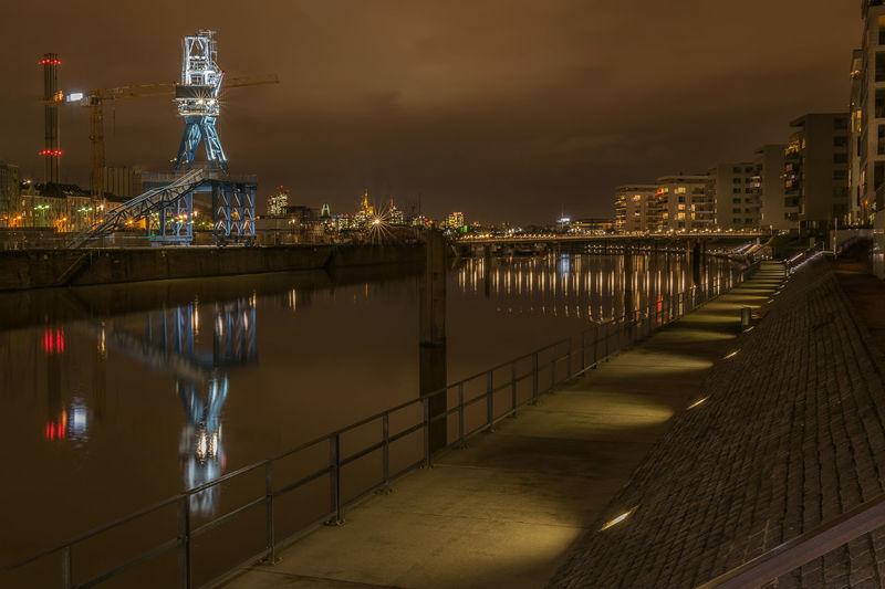 River amidst illuminated city against sky at night