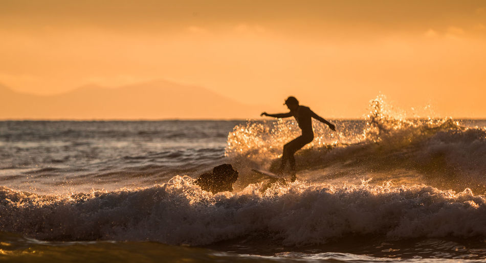 Silhouette man surfing in sea against sky during sunset