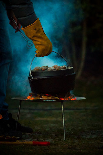 Barbecue Barbecue Grill Burning Close-up Dutch Oven Flame Food Food And Drink Freshness Heat - Temperature Human Body Part Human Hand Leisure Activity Low Section Meat Men Night One Person Outdoors People Preparation  Preparing Food Real People Serving Tongs Smoke - Physical Structure