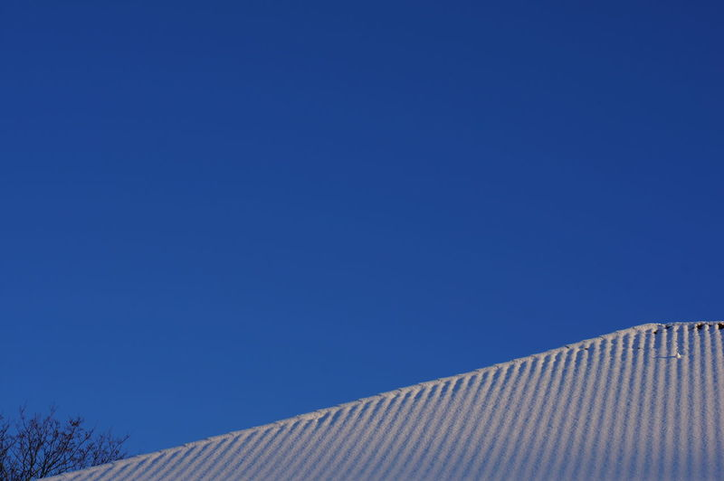 Roof of building against clear blue sky