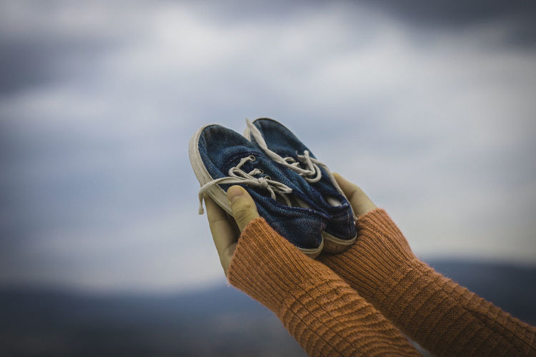 Cropped Hands Holding Shoes Against Sky