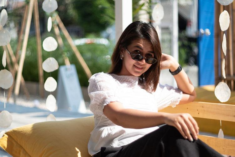 Full length of woman sitting on sunglasses