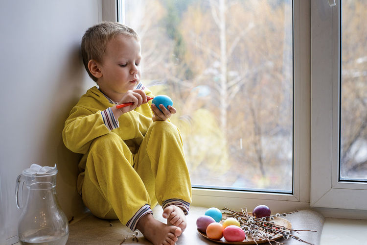 Full Length Of Cute Boy Holding Easter Egg While Sitting On Window Sill At Home