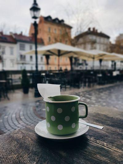 Green polka dot tea cup, empty city street.