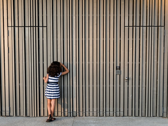 Curiosity Saint Julien En Genevois Curiosity Streetphotography Street Photo De Rue Fille Stripes Bois Wood - Material Kids Enfant Girl Childhood Child Full Length Standing Pattern Closed Locked Closed Door Door Gate Keyhole Door Knocker Doorknob Lock Entryway Door Handle Entry EyeEmNewHere