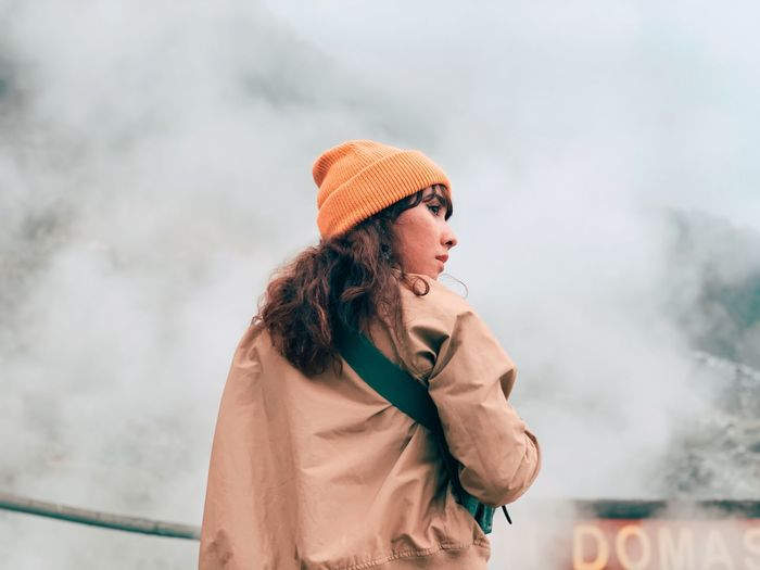 Low angle view of woman looking away against fog