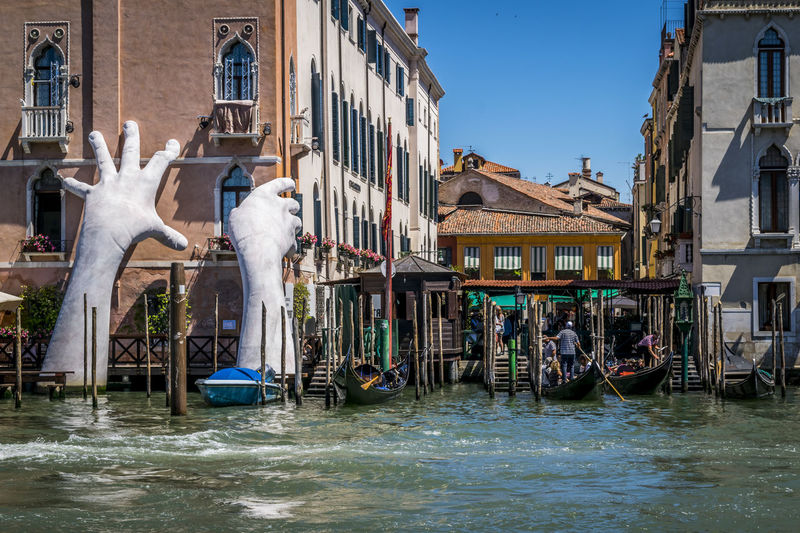 """Artwork titled """"Support"""" emerges from Grand Canal, by Lorenzo Quinn. The contemporary sculpture of giant hands was unveiled during the opening of the 2017 Venice Biennale. 2017 BIG Be. Ready. Famous Giant Grand Canal Hands Quinn Reflection SUPPORT Tourist Venice, Italy Architecture Art Background Biennale Buildings Change Gondola - Traditional Boat Lorenzo Monumental  Rise Speedboat Veneto Water"""