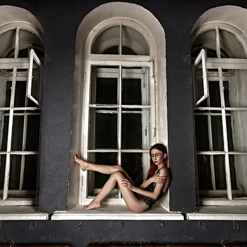 Portrait of young woman sitting on window