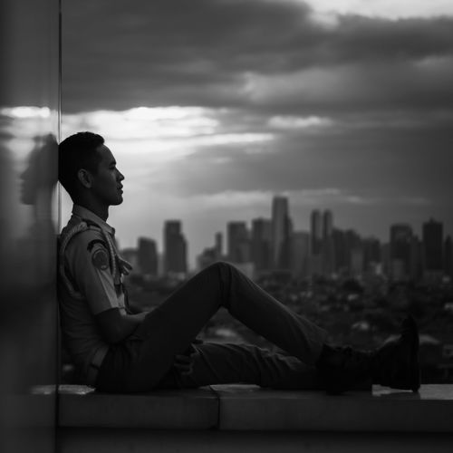 Side view of a man sitting against cityscape