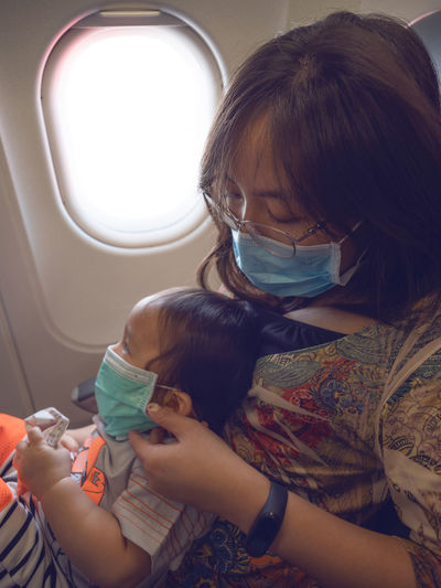 Mother and son wearing masks while sitting in airplane