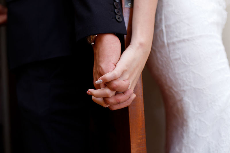 Close up wedding couple holding hands Care Couple Hand In Hand Love Relationship Wedding Adult Adults Only Bonding Close-up Day Human Hand Indoors  Men Midsection People Real People Standing Togetherness Two People Women A New Beginning Human Connection