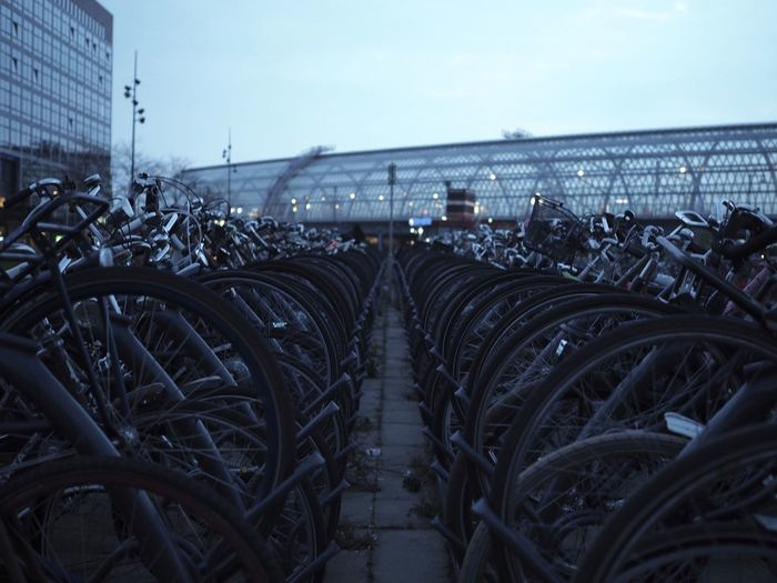 Bicycles parked in city against sky