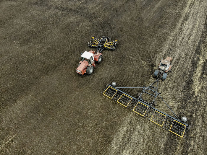 Aerial view of a modern tractor plowing dry field, preparing land for sowing Aerial Agriculture Field Tractor Farm Ground Soil Countryside Combine Machinery Motion Working Plowing High Angle View Agricultural Machinery Aerial View Land Vehicle Environment Agricultural Equipment Outdoors Landscape