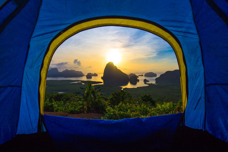 Scenic view of sunset seen through tent