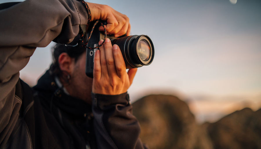 Midsection of man holding camera against sky