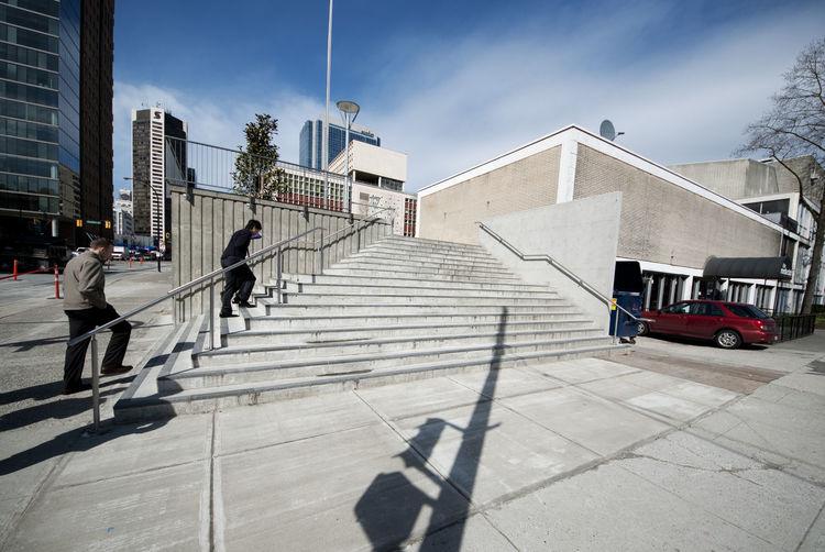 People walking on steps in city against sky