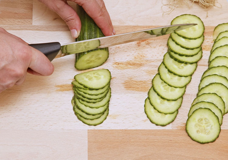 Upper view of hands with a knife chopping a cucumber. Food And Drink Food Human Hand Healthy Eating Human Body Part Hand Freshness SLICE Vegetable Cutting Board One Person Green Color High Angle View Preparing Food Finger Knife Chopping Slicing Cucumber Salad