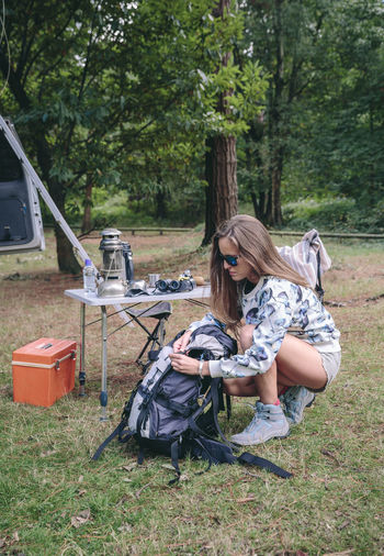 Woman Packing Backpack On Field In Forest