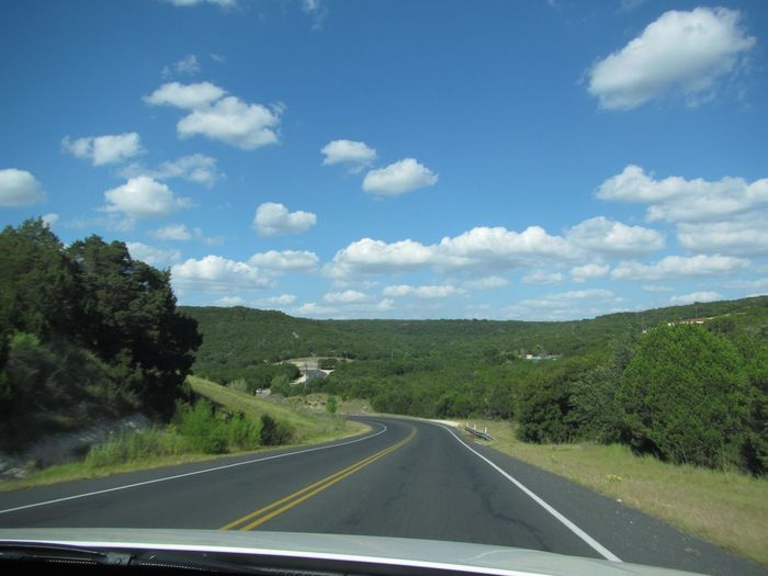 Road amidst landscape against sky seen through car windshield