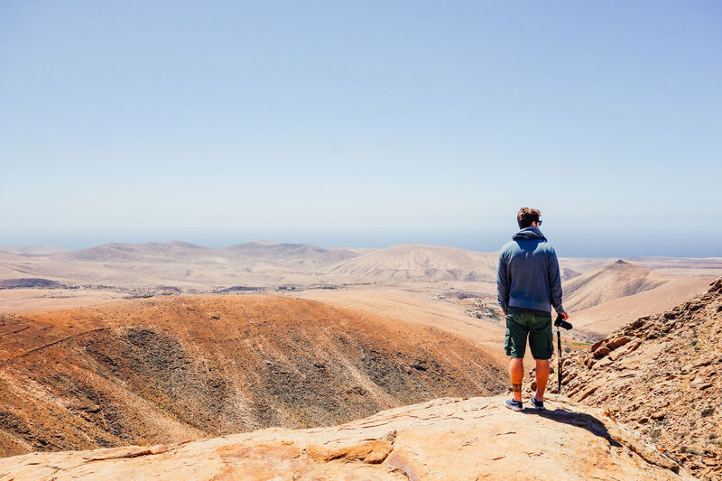 Rear view of man standing on rock looking at landscape against blue sky