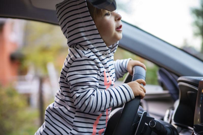 Cute girl holding steering wheel