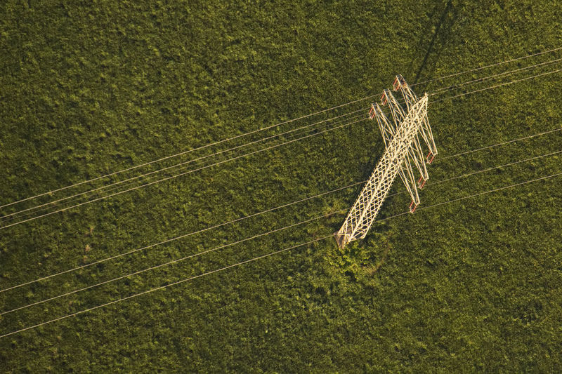 High angle view of electricity pylon on grassy field