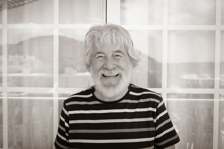 Portrait of smiling man against window