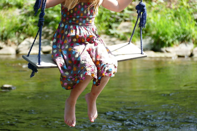 Low section of girl swinging over lake