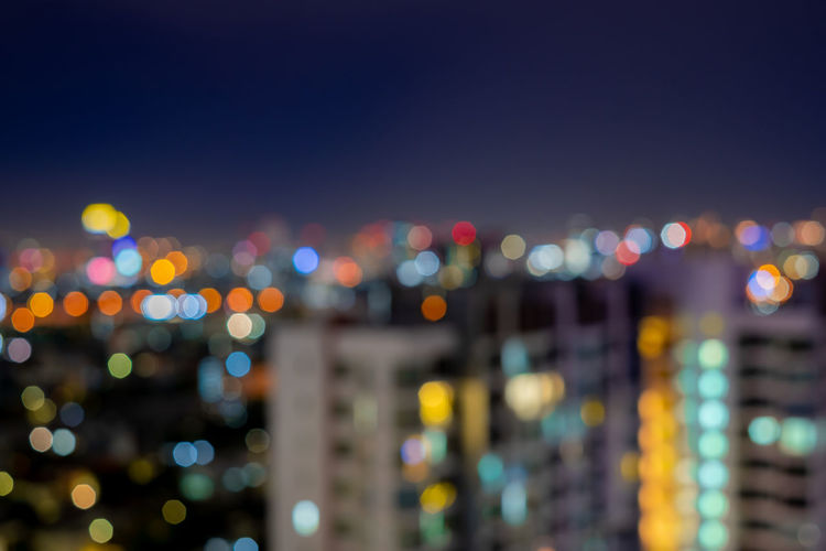 Defocused image of illuminated cityscape against sky at night