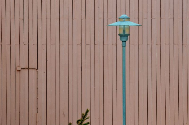 Low angle view of lamp against wall