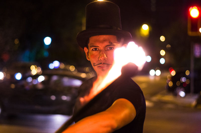 Portrait of man performing with fire in city at night